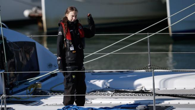 Greta saluda desde el catamarán a su llegada a Lisboa, donde la esperan medios y ciudadanos.