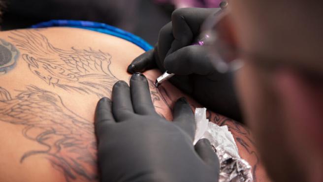 Tatuador haciendo un tatuaje
