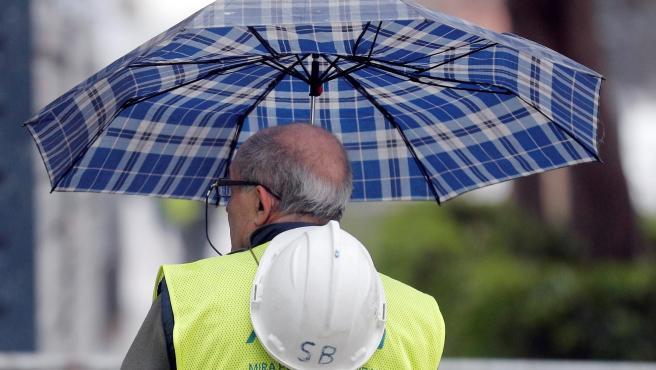 Un trabajador se protege de la lluvia en Valencia.