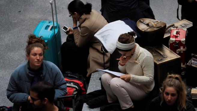 Varios pasajeros esperan la salida de su tren en la estación de Atocha, en Madrid.