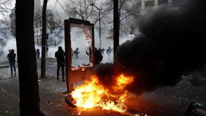 Un poste publicitario arde durante la manifestación por las pensiones en París.