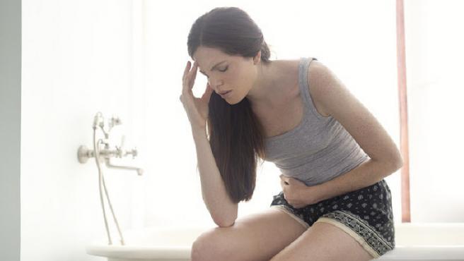 Una mujer sentada en el baño mientras se queja del estómago y la cabeza