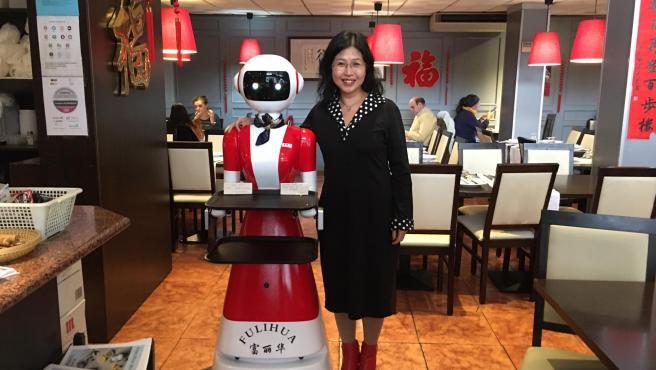 La dueña del restaurante chino Fulihua, Keke Luo Zhao, junto al robot.