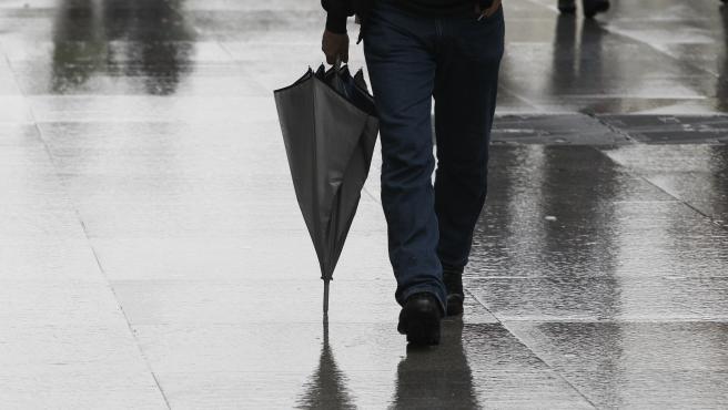 Una persona camina con un paraguas un día de lluvia.
