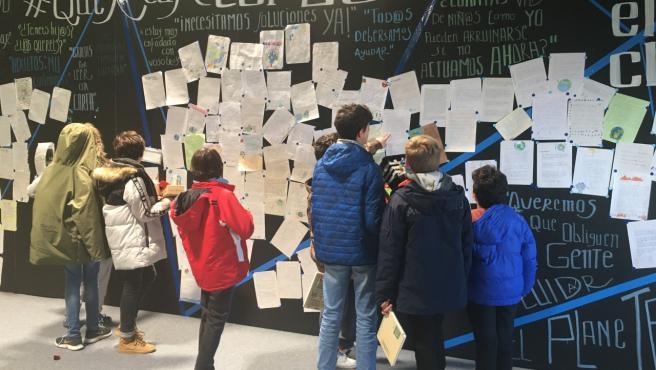 Un grupo de niños busca sus cartas en el mural que Madres por el Clima ha creado en la COP25.