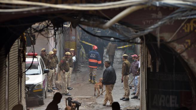 Agentes de policía y bomberos en la zona próxima a la fábrica de Nueva Delhi incendiada.