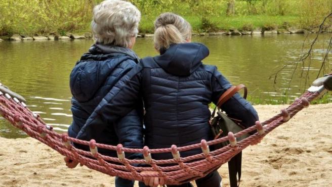 Imagen de archivo de una mujer sentada junto a su hija frente a un lago.