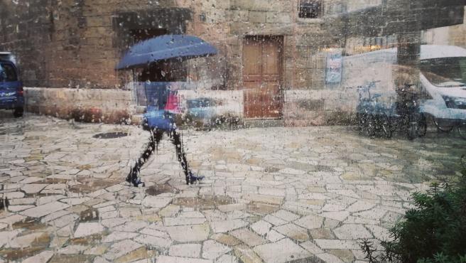 Una mujer pasea por el centro de Palma con un paraguas, vista a través de un cristal con gotas de lluvia.