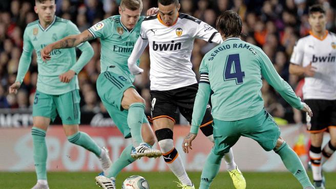 Rodrigo disputa el balón con Kroos y Ramos