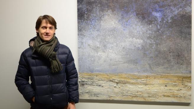 Carlos López junto a uno de los cuadros de la exposición