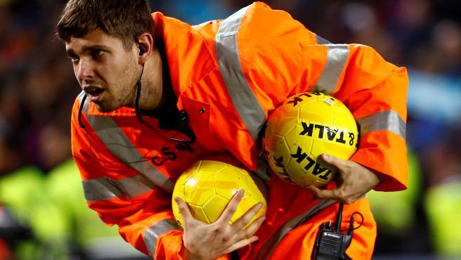 Un steward retira balones amarillos lanzados al Camp Nou