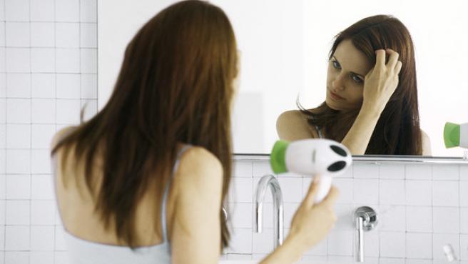 Una mujer alisándose el pelo con un secador