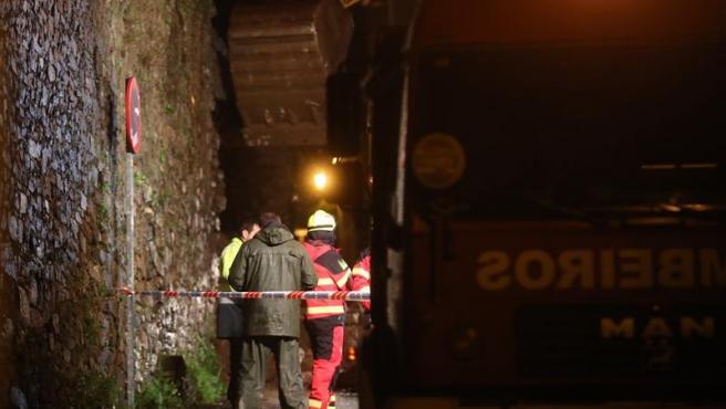Bomberos y efectivos de emergencias, en la zona del parque de San Domingos de Bonaval, en Santiago de Compostela. donde el derrumbe de un muro provocó la muerte de un hombre.
