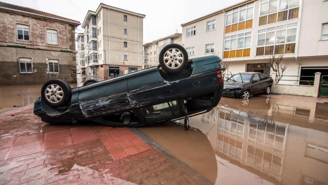 Un coche volcado en Reinosa tras las mayores inundaciones de su historia.