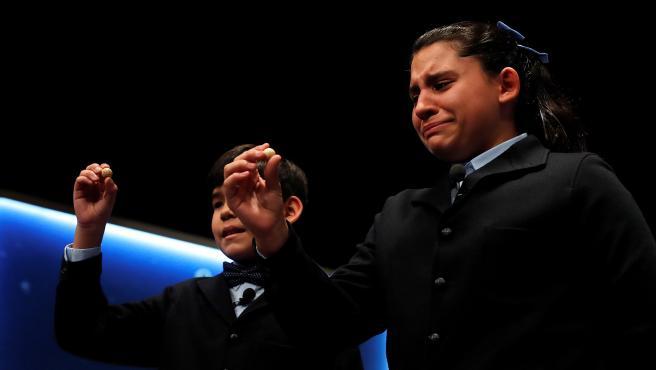 La niña Nerea Pareja que, junto a su compañero del colegio de San ildefonso Alfonso Dávalos (i), ha cantado el primero de los quintos premios, el 75206.