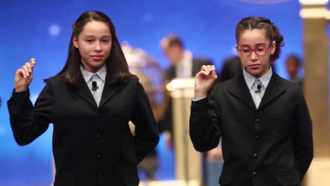 Las dos niñas de la residencia de San Ildefonso, Noura Akrouh (dech) y Elisabeth del Carmen Roque Figuereo (izq), posan con las bolas correspondientes al Primer Premio de la Lotería de Navidad, el Gordo de la Lotería, con el nº 26.590, el cual ha salido