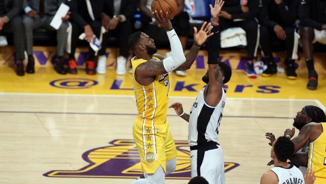 LeBron James intenta lanzar a canasta ante Paul George.