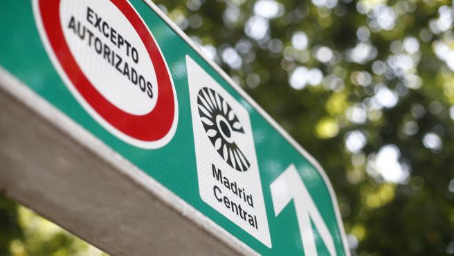 Señal con símbolo de prohibido aparcar al lado del distintivo de Madrid Central.