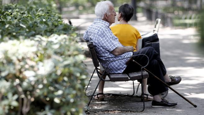 Un pensionista descansa en un banco de un parque de Madrid.
