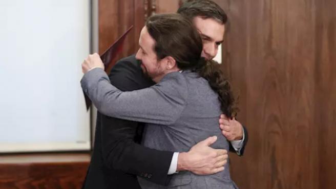 Pedro Sánchez y Pablo Iglesias (dech), se dan un abrazo durante el acto de presentación del programa de Gobierno del PSOE y Unidas Podemos, en el Congreso.