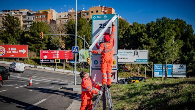 Operarios instalando las señales de tráfico definitivas de la ZBE Rondas BCN en el ramal de la salida 14 Besòs de la Ronda de Dalt, en L'Hospitalet de Llobregat