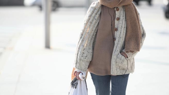 Una mujer abrigada con bufanda y chaqueta pasea con una bolsa en la mano.