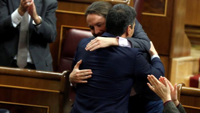El líder de Unidas Podemos, Pablo Iglesias, abraza a Pedro Sánchez tras intervenir ante el pleno del Congreso en la primera jornada de la sesión de investidura de Sánchez.