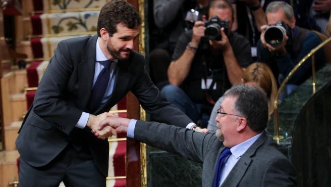 El presidente del PP, Pablo Casado, da la mano al diputado de Foro Asturias en el Congreso, Isidro Martínez Oblanca, tras la intervención de éste en el turno de réplica al presidente del Gobierno en funciones, Pedro Sánchez.