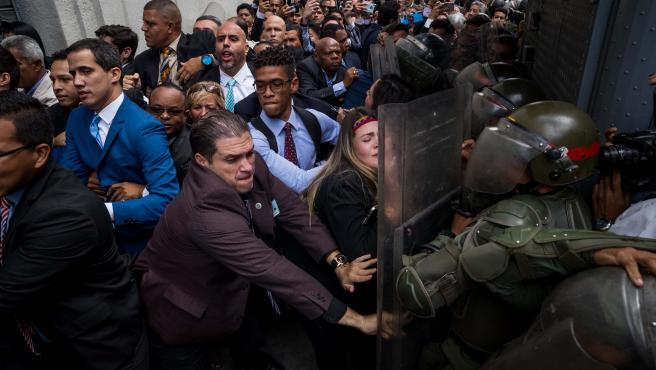 Juan Guaidó (izquierda) y otros diputados opositores venezolanos forcejean con miembros de la Guardia Nacional Bolivariana para ingresar a la Asamblea Nacional, en Caracas (Venezuela).