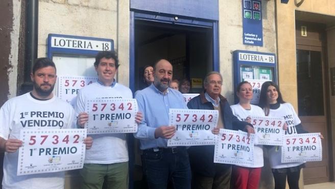 El propietario de la Administración de Lotería 18 de Santander, Manuel Puente (en el centro con camisa azul), con el número del primer premio del Sorteo del Niño, del que ha vendido un décimo