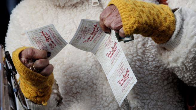 Una lotera entrega una tira de boletos de la Lotería del Niño.