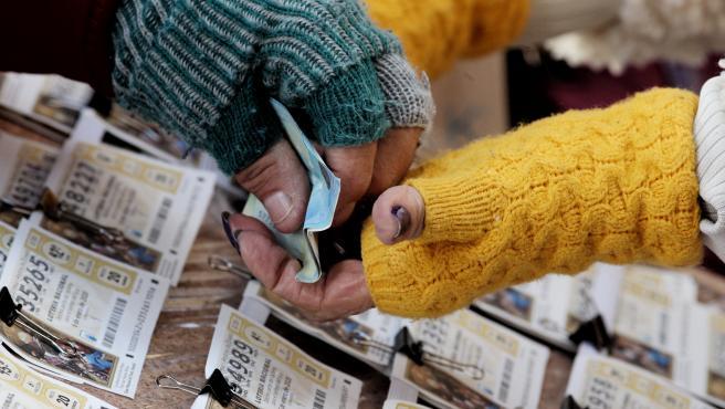 Una mujer comprando un boleto de la Lotería del Niño.