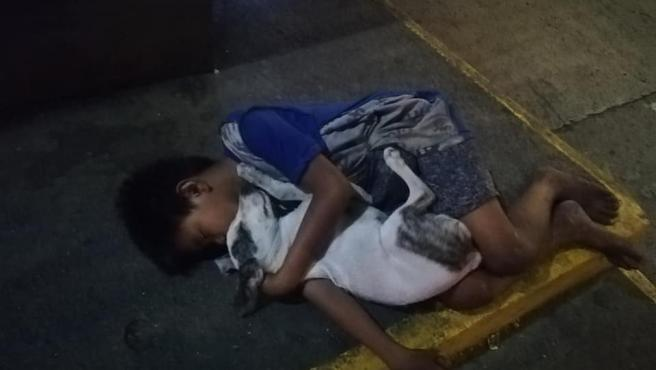 El niño, durmiendo sobre una acera junto a un perrito.