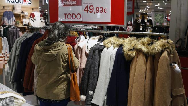 Una mujer examina varias prendas de abrigo durante el inicio de las rebajas este martes en Madrid.