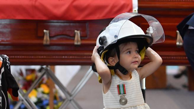 Charlotte O'Dwyer, hija del bombero fallecido con el casco de su padre durante un funeral.