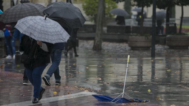 Personas se protegen de la lluvia bajo sus paragüas