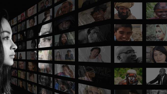 Una mujer mira una pantalla con muchas fotos