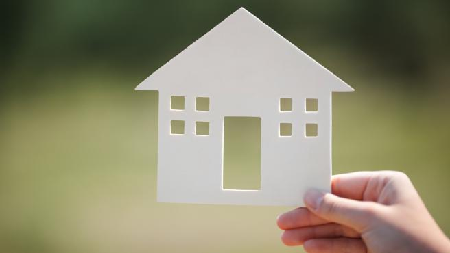 Close-up shot of female hands holding small house model on the background of defocused green nature. Real estate, mortgage, eco or country house concept