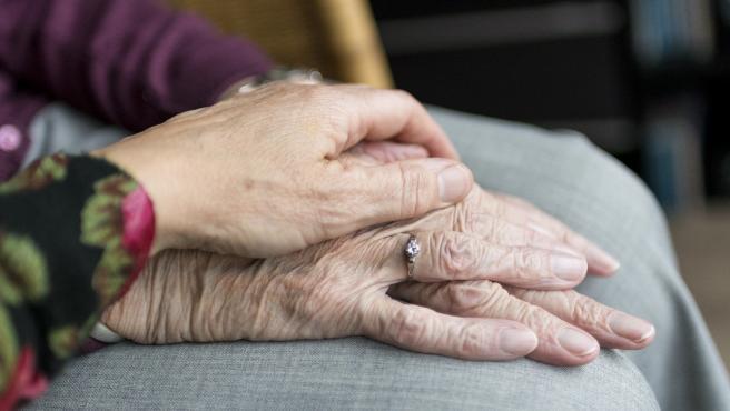 Imagen de archivo de dos ancianos dándose la mano.