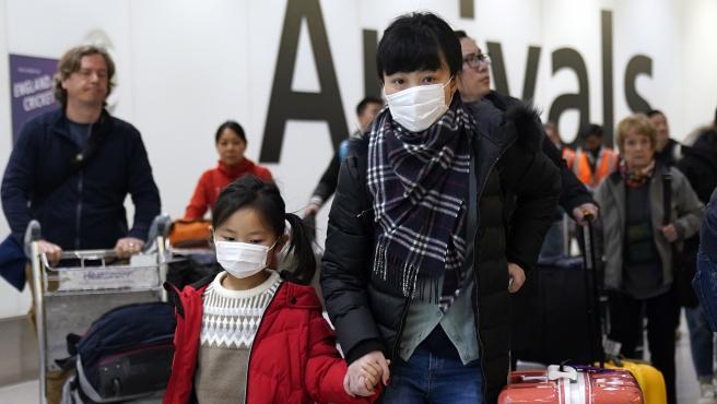Pasajeros chinos llegan al aeropuerto de Londres.