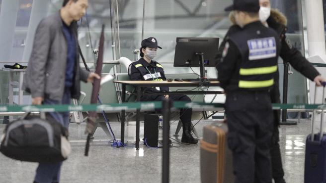La seguridad del aeropuerto usa una máscara en Guangzhou, provincia de Guangdong, China.