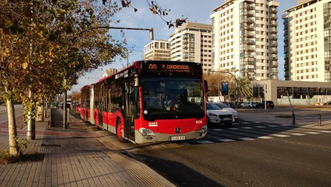 Un bus articulado híbrido de la línea 99 de la EMT circula por València.