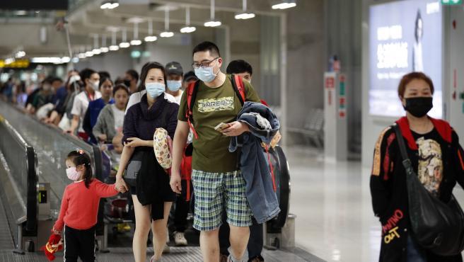 Pasajeros con mascarillas en el aeropuerto tailandés de Suvarnabhumi.
