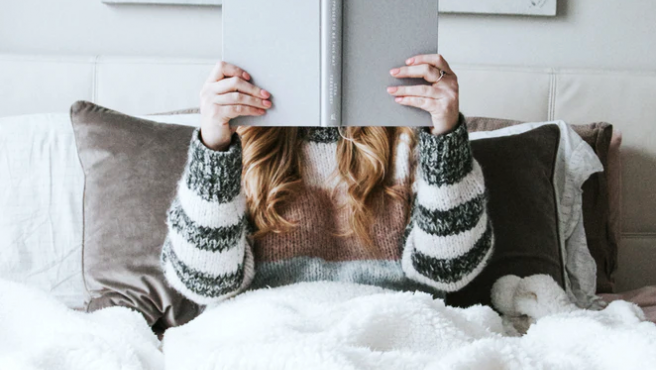 Una mujer joven leyendo un libro en la cama