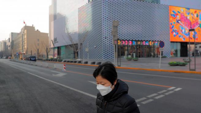 Una mujer con mascarilla en una calle vacía de Beijing, China.