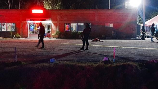 Policías federales caminan por el sitio donde fueron asesinados al menos 9 personas la noche del viernes al pie de una carretera en Villagrán, Guanajuato.