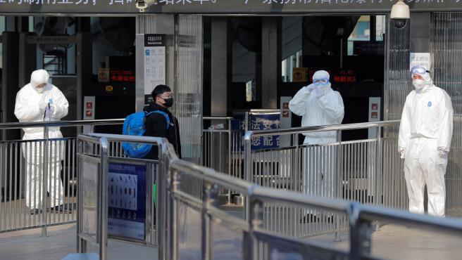 Miembros de seguridad protegidos con trajes aislantes esperan a la entrada del metro para tomar la temperatura a los pasajeros en Pekín, China, este 25 de enero.