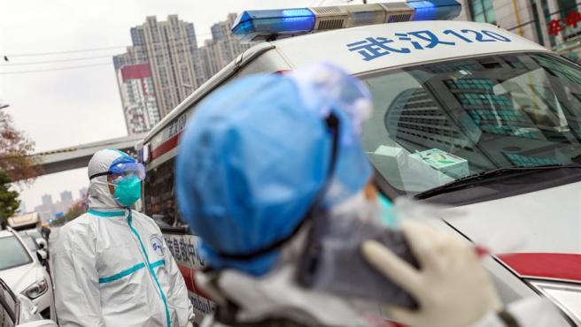 Personal médico con protección para evitar contagios, junto a una ambulancia en un hospital de Wuhan, China.