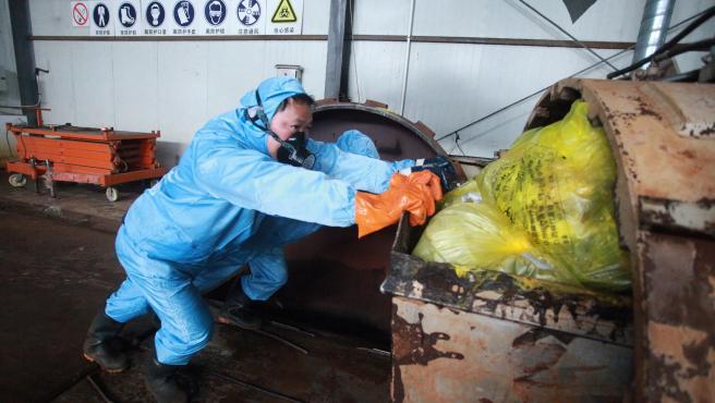 Trabajadores depositan residuos médicos de enfermos de coronavirus en una empresa de tratamiento de Yangzhou.