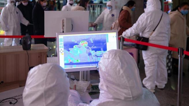 Personal médico utiliza imágenes térmicas visibles e infrarrojas para revisar la temperatura de los pasajeros en Nanjing (China), ante posibles casos del coronavirus de Wuhan.